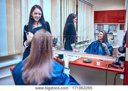 Young beautiful woman discussing hairstyling with her hairdresser holding a comb and scissors while sitting in the hairdressing salon