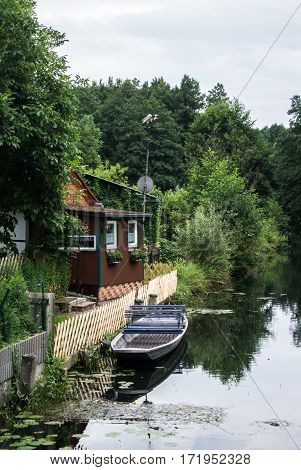 Traditional german house near the channel with a garden a a boat under the old high trees.