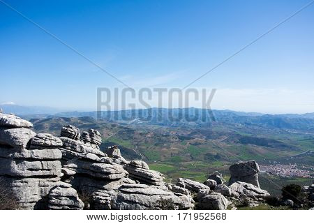 A view to mountains and villages from observation deck at natural park El Torcal in Spain.