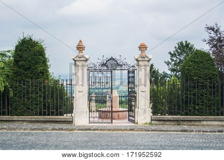 The gate to the garden on the top of the hill on a cloudy day with the panorama of fields Pannonhalma Abbey Gyor Hungary.