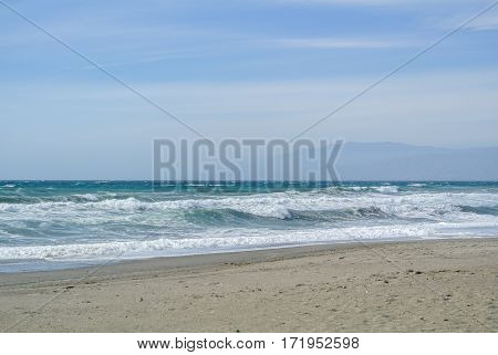 Sea waves at the lonely beach and a view to the distant mountains on cloudy windy day at Cabo de Gata natural park Andalusia Spain.