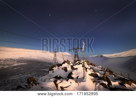 Support of the high-voltage line. A winter night mountain landscape with the star sky.