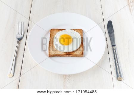 fried egg on toast. whtie background. studio shot