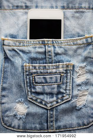 technology and communication concept - smartphone in pocket of denim overalls