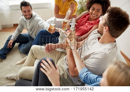 friendship, drink, alcohol, holidays and people concept - happy friends drinking beer at home party