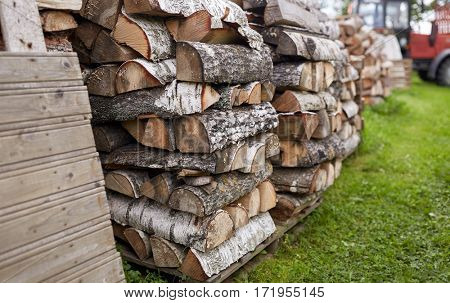 heating, agriculture and farming concept - stack of firewood on farm at country