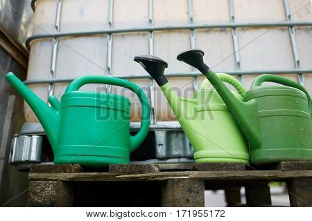 farming, gardening and agriculture concept - watering cans at farm water tank