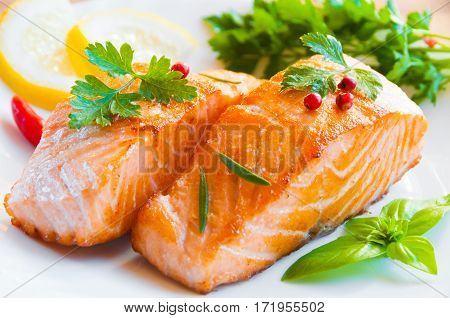 Cooked salmon fish fillets with herbs and lemon