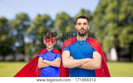 family, power and people concept - man and boy wearing mask and red superhero cape over summer park background