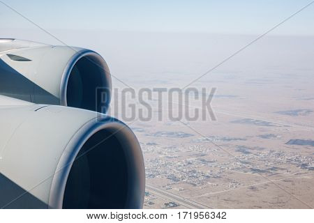 Airliner jet engines and desert landscape, airplane in flight