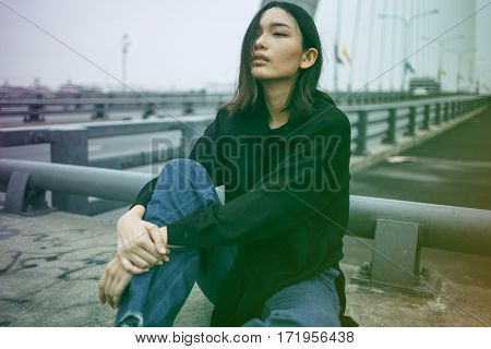 Asian ethnicity girl is on a bridge shoot.
