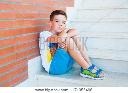 7 year old boy sitting on stairs