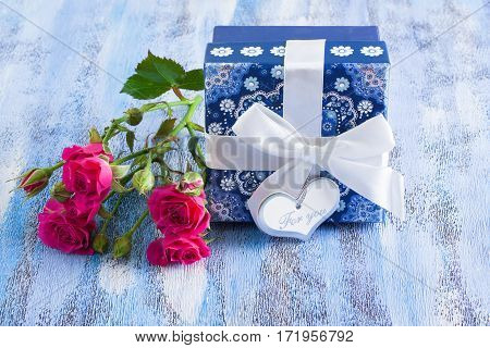 Blue Present Box And Pink Roses On Wooden Tray