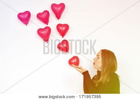 Woman blowing balloon heart love kiss