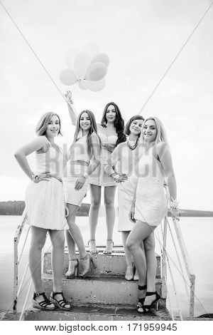 Five Girls With Balloons At Hand Weared On White Dresses On Hen Party Against Pier On Lake.