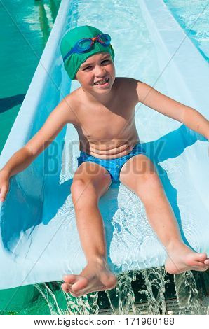 Smiling child on water slide in aqua park