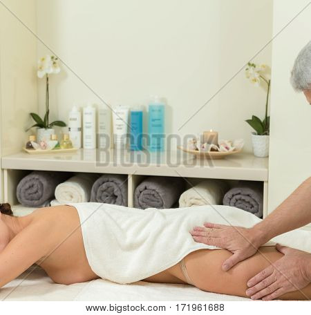 Masseur doing massage on woman legs in the spa salon