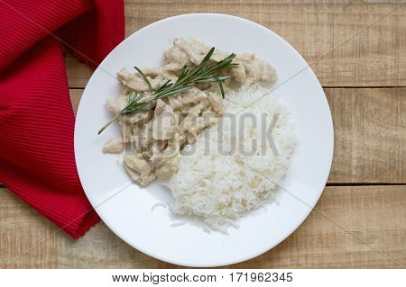 Top view of cooked chicken with white sauce and rosemary and served on wooden table with red napkin. Healthy eating concept