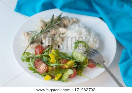 Portion of fresh vegetables salad with white rice and slices of chicken breasts served on a white plate with blue kitchen towel and fork