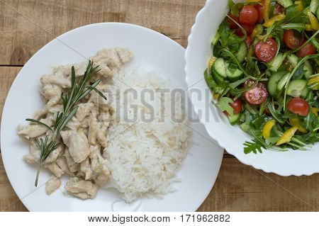 White rice with chicken slices in white sauce and with fresh rosemary and big salad bowl with cucumber arugula cherry tomatoes and yellow capsicum. Balanced eating concept.