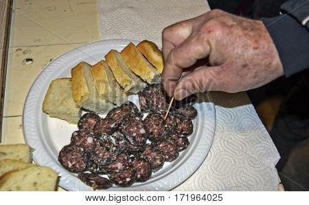 Tasting sausage and bread on a plate.