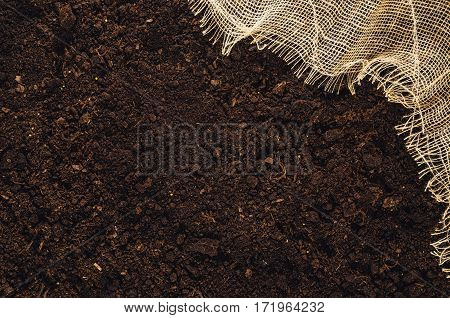 Fertile soil texture background with jute or linen cloth seen from above, top view. Gardening or planting concept with copy space. Natural pattern