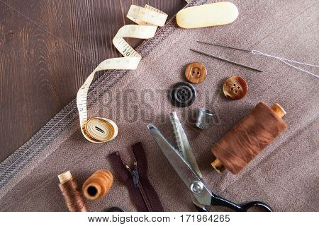 Set. Scissor, Buttons, Zip, Tape Measure, Thread And Thimble On Fabrics On Dark Wooden Background, F