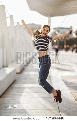 Funny Blonde Woman Jumping In Urban Background.