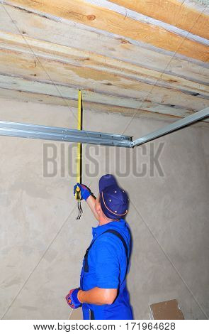 KYIV, UKRAINE - March 1, 2017: Contractor with measuring tape Installing Garage Door Post Rail and Spring Installation and Garage Ceiling. Garage Door Installation Step by Step.