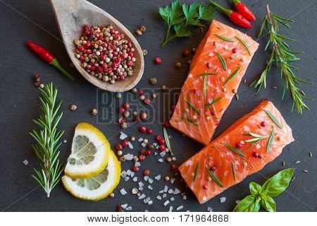 Uncooked salmon fillets with herbs ob black