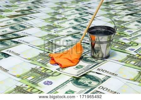 Laundering of money. A bucket of water is worth on the euro and the dollar. next to a mop with a rag