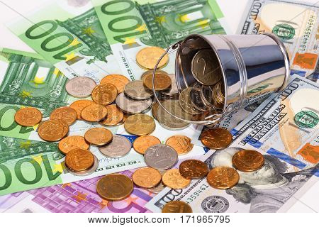 Euro, dollars and bucket with Russian money. Inverted bucket with Russian small coins lying  on the euro and dollar. Concept of exchange rates