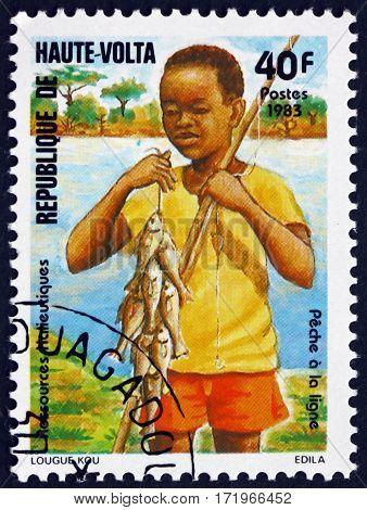 BURKINA FASO - CIRCA 1983: a stamp printed in Burkina Faso shows Boy fishing fishing resources circa 1983