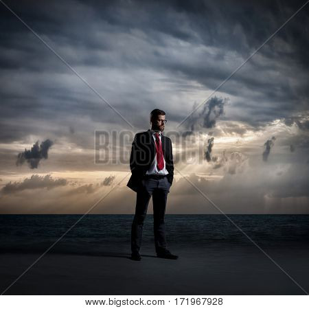 Businessman standing over dark, dramatic ocean background. Business concept.
