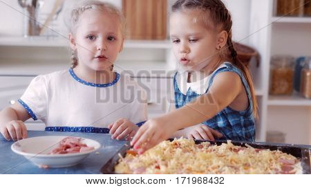 Little girls sprinkle pizza with cheese, cooking food