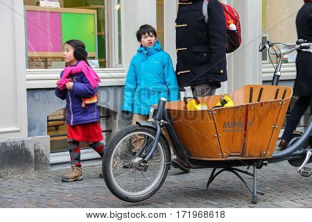Utrecht the Netherlands - February 13 2016: People walk past a bike with big wooden cargo compartment on sidewalk