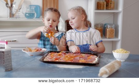 Little girls preparing pizza from ingredients, cooking food