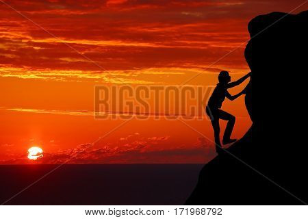Teamwork couple hiking help each other trust assistance silhouette in mountains sunset. Teamwork of man and woman hiker helping each other on top of mountain climbing team