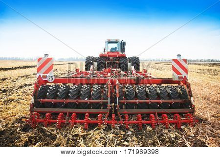 Modern tractor in the field with complex for the treatment and plowing of soil. The concept of work in a fields and agriculture industry.