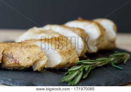 Slices of baked and fried chicken breast cooked with rosemary and served on black slate board