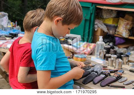 Two boys looking at souvenirs in the market of Schodnica Ukraine