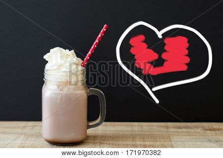 Jar with hot chocolate drink with whipped cream and red paper straw with polka dot pattern and hand-drawn heart