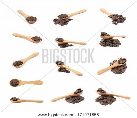 Pile of cooking chocolate teardrop shaped chips with a serving wooden spoon over it, composition isolated over the white background, set of multiple different foreshortenings
