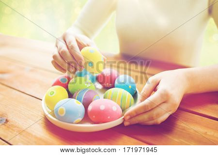 holidays, tradition and people concept - close up of woman hands with colored easter eggs on plate over green lights background