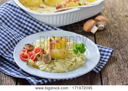 Hearty potato dumpling  gratin with cheese and bacon served on warm coleslaw