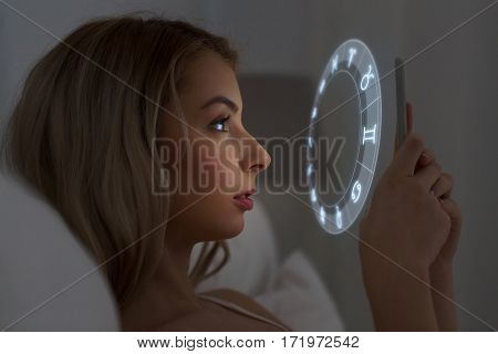 technology, astrology and people concept - young woman reading horoscope on smartphone in bed at home at night