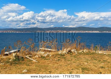 Black Sea coast. Coastline with dry yellow grass. Bay View. Sunny Beach mountains and houses on the horizon. Blue sky with cumulus clouds.