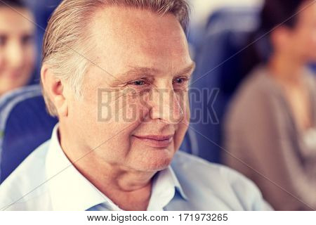 transport, tourism, trip and people concept - happy senior man sitting in travel bus or airplane