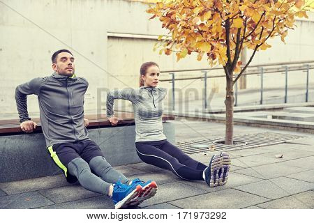 fitness, sport, exercising, training and people concept - couple doing triceps dip exercise on city street bench poster