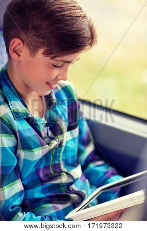 transport, tourism, road trip, technology and people concept - happy boy with tablet pc computer in travel bus or train